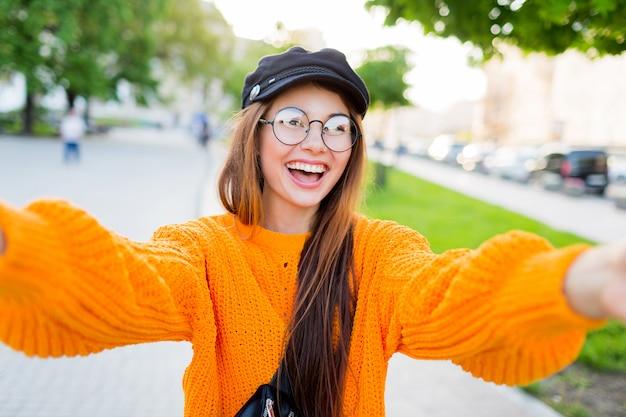 Frohes lächelndes brünettes mädchen in runden brillen und im trendigen orange gestrickten pullover, der selbstporträt macht