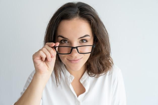 Frohes lächelndes mädchen, das gläser löscht. junge kaukasische frau, die über brillen späht.