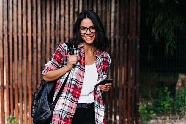 Frohes lateinisches weibliches modell, das positive emotionen während des fotoshootings auf holzwand ausdrückt. entspanntes brünettes mädchen, das rucksack und telefon hält.
