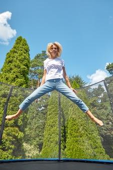 Frohes mädchen, das auf eine trampoline im park springt. stadturlaub, outdoor-aktivitäten.