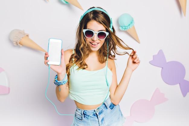 Frohes mädchen in blauen accessoires, das musik in ihrem zimmer hört, smartphone hält und mit haaren spielt. porträt der eleganten jungen frau in den gläsern mit der lockigen erstaunlichen frisur, die auf lila wand aufwirft.