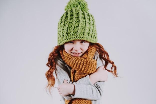 Frohes mädchen in der strickmütze und im schal zeigt, dass einfriert.