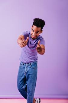 Frohes mann in vintage blue jeans, die mit erfreutem gesichtsausdruck suchen. blithesome brünette kerl, der positive gefühle ausdrückt.