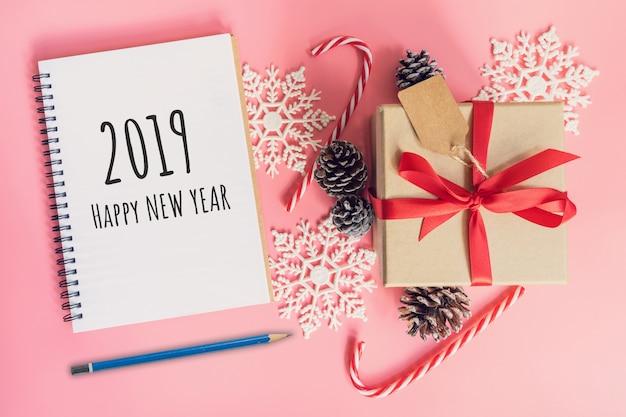 Frohes neues jahr 2019, draufsicht braune geschenkbox, notizbuch und weihnachtsdekoration