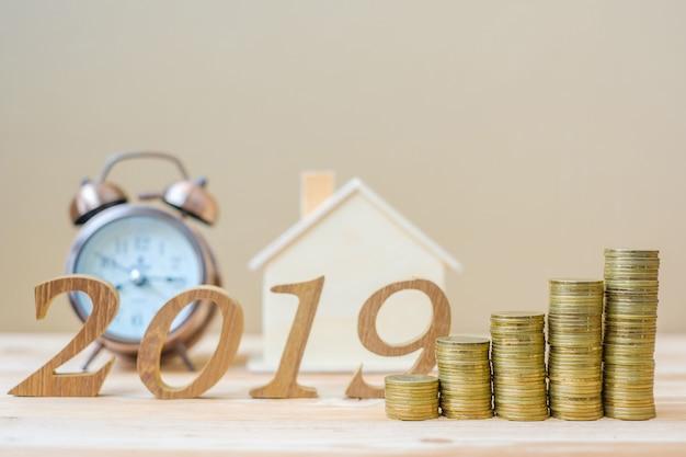 Frohes neues jahr 2019 mit goldmünzenstapel und hölzerner zahl