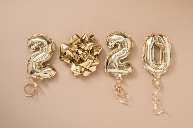 Frohes neues jahr 2020 feiern. goldfolie steigt die nr. 2020 im ballon auf, die auf beige pastellhintergrund lokalisiert wird