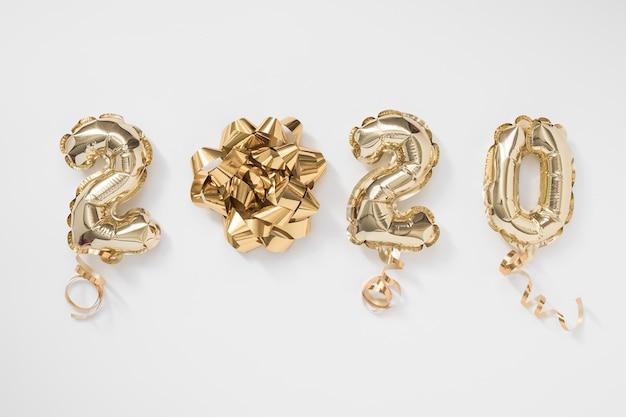 Frohes neues jahr 2020 feiern. goldfolie steigt nr. 2020 auf weißem hintergrund im ballon auf