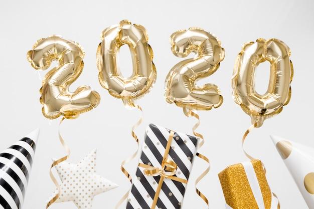 Frohes neues jahr 2020 feiern. goldfolie steigt nr. 2020 auf weißem hintergrund mit geschenken im ballon auf