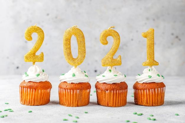 Frohes neues jahr 2021, cupcakes mit goldenen kerzen.