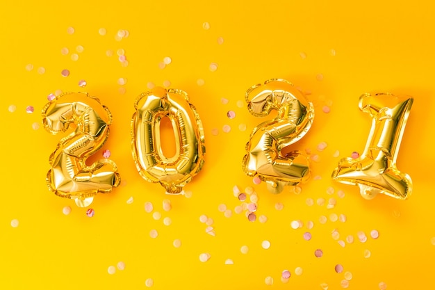 Frohes neues jahr 2021 feiern. helle goldene luftballons mit glitzersternen auf gelbem hintergrund.