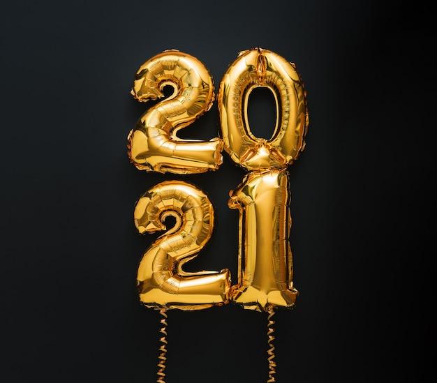 Frohes neues jahr 2021 gold luftballon text mit bändern auf schwarz.