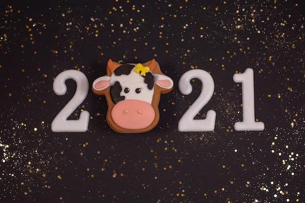 Frohes neues jahr 2021 mit goldenen glitzersternen und lebkuchenbullen
