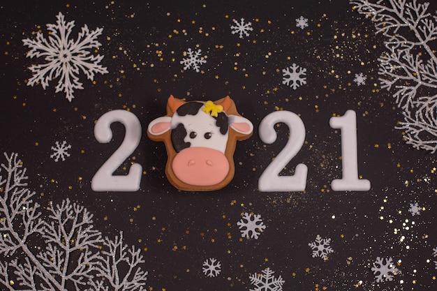 Frohes neues jahr 2021 mit lebkuchenbullen und schneeflocken