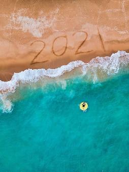 Frohes neues jahr 2021, schriftzug am strand mit welle und blauem meer.