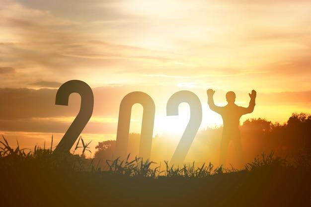 Frohes neues jahr 2021 silhouette-konzept menschliches stehen mit nummer mit schönem orange himmel für wechsel zum neuen jahr 2021.