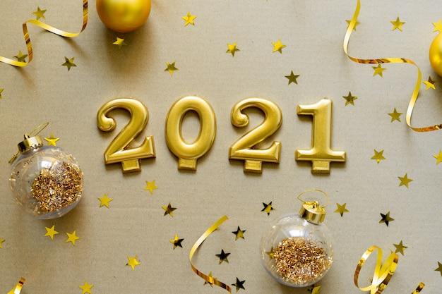 Frohes neues jahr 2021. weihnachtshintergrund mit goldenen verzierungen, kugeln, konfetti. weihnachtsfeiertagsfeier, winter, neujahrskonzept.