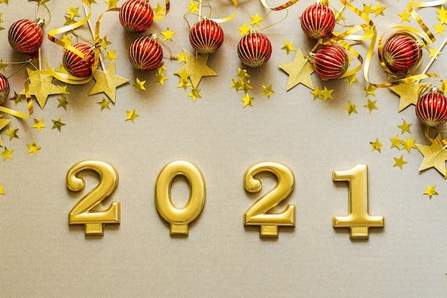 Frohes neues jahr 2021. weihnachtshintergrund mit roten verzierungen, kugeln, konfetti. weihnachtsfeiertagsfeier, winter, neujahrskonzept.