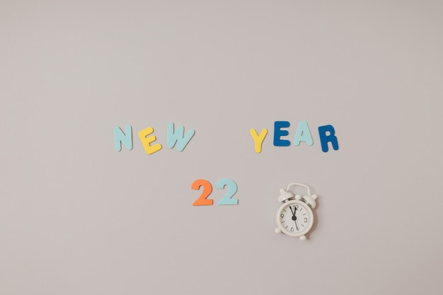 Frohes neues jahr 2022 buchstabiert mit bunten kerzen und schaumstoffaufklebern auf grauem und violettem hintergrund. platz kopieren, flach legen.