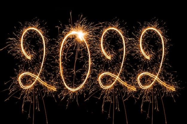 Frohes neues jahr 2022 funkelnder brennender text frohes neues jahr 2022 auf schwarzem hintergrund isoliert