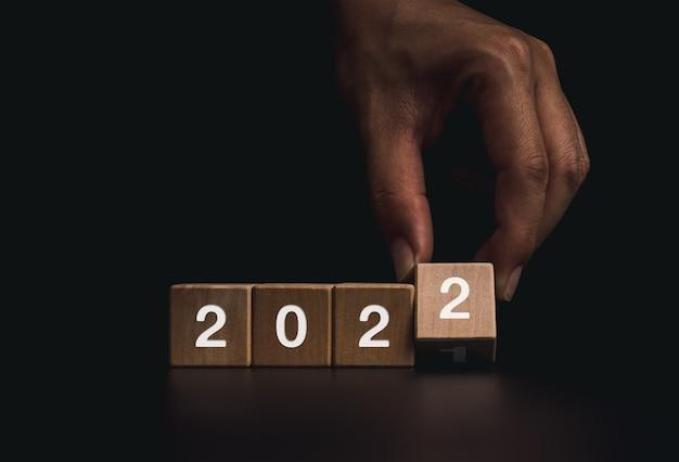 Frohes neues jahr 2022 konzept. handumdrehen von holzwürfelblöcken für die änderungsnummer von 2021 bis zum neuen jahr 2022 auf dunklem hintergrund, modernem und minimalistischem stil.