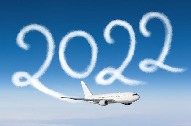 Frohes neues jahr 2022 konzeptreisen auf dem hintergrund unter cloudscape. zeichnung von passagierflugzeug-dampfkondensstreifen im himmel.
