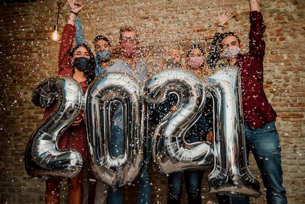 Frohes neues jahr! gruppe der jungen leute, die gesichtsmaske feiern, die 2021 feiert