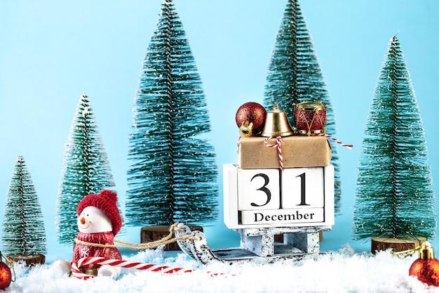 Frohes neues jahr-grußkarte. geschenkbox auf holzschlitten. feiertagsbaum auf blauem schneehintergrund mit kopienraum. frohe weihnachten und ein glückliches neues jahr-konzept