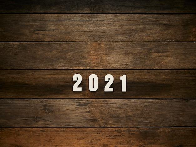 Frohes neues jahr hintergrund mit 2021 figuren auf rustikalem dunklem holzhintergrund. platz für text