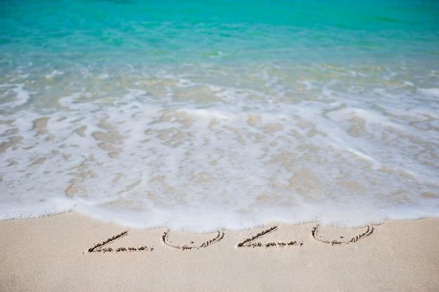 Frohes neues jahr in den weißen sand geschrieben