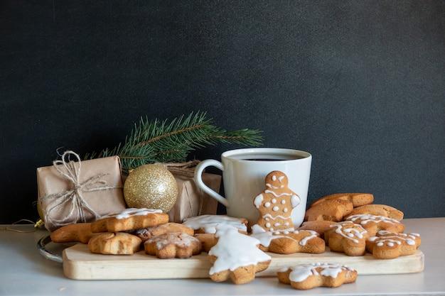 Frohes neues jahr lebkuchen aus ingwerkeksen glasierte zuckerglasurdekoration auf schwarzem hintergrund, minimales saisonales pandemie-winterurlaubsbanner