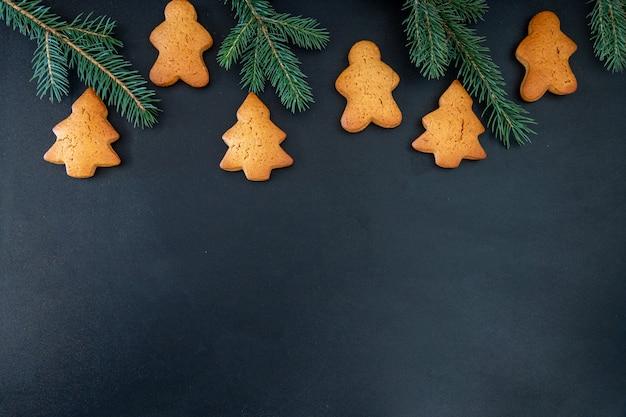 Frohes neues jahr lebkuchen aus ingwerkeksen mann glasierte zuckerglasur dekoration auf schwarzem hintergrund, minimale saisonale pandemie winterurlaub banner