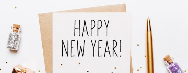 Frohes neues jahr mit umschlag, geschenken und goldenen glitzersternen auf weißem hintergrund. frohe weihnachten und neujahrskonzept