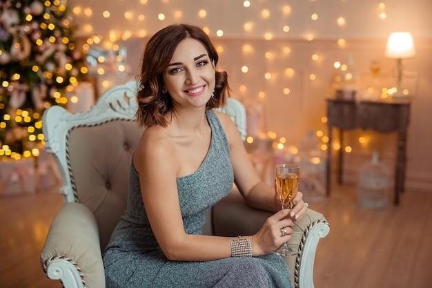 Frohes neues jahr! schöne frau im abendkleid mit einem glas champagner in den händen
