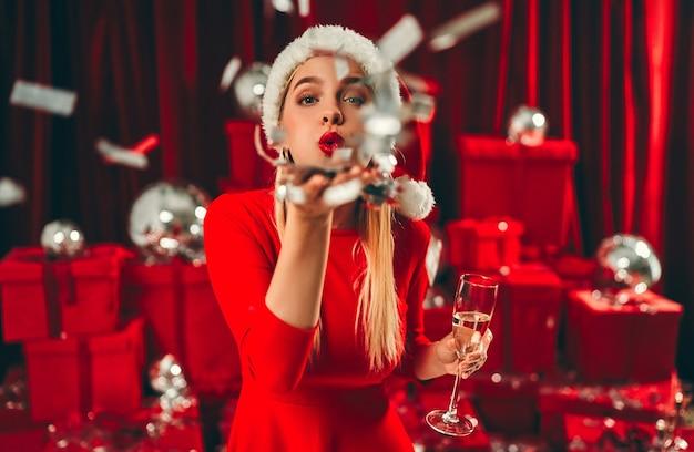 Frohes neues jahr! schöne sexy frauenblondine in der weihnachtsmütze mit glas champagner bläst konfetti von der handfläche. neujahrsfeier. heiligabend.