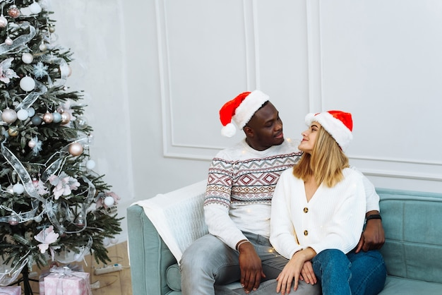 Frohes neues jahr und frohe weihnachten zu hause zusammen. lächelnder junger afroamerikaner und kaukasische dame in weihnachtsmannmützen, umarmung und blick in die kamera im wohnzimmer mit baum und girlanden.