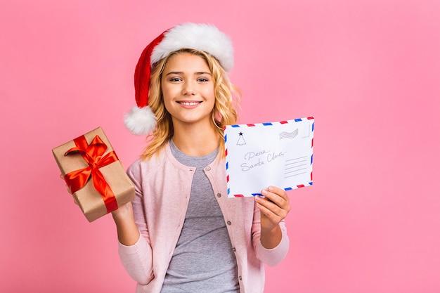 Frohes neues jahr und weihnachten! nettes blondes mädchen des kleinen jugendlichen teenagers mit brief an den weihnachtsmann