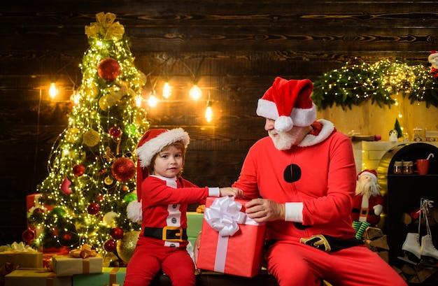 Frohes neues jahr weihnachtsmann-mann und kleiner weihnachtsmann-junge mit weihnachtsdekoration weihnachtszeit glücklich