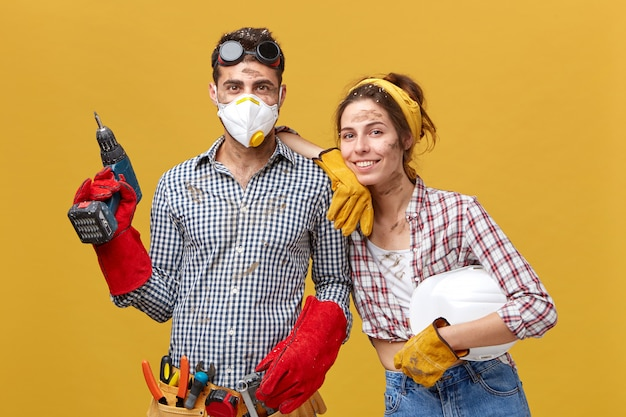 Frohes paar mit schmutzigen gesichtern in freizeitkleidung, die bohrer und helm in ihrem haus repariert. männlicher junger attraktiver hausbesitzer in den schutzhandschuhen und in der maske, die etwas in wand bohren