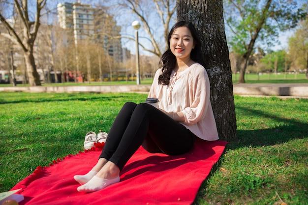 Frohes positives asiatisches mädchen, das draußen wochenende genießt