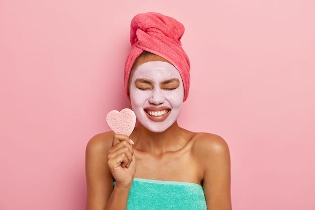 Frohes weibliches model lächelt breit, zeigt weiße zähne, hält herzförmigen kosmetischen schwamm, hält die augen vor vergnügen geschlossen