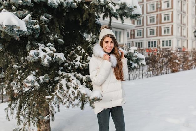 Frohes weibliches modell im trendigen outfit, das wintertage während des spaziergangs im park genießt. außenporträt der lachenden frau, die zeit auf der straße im frostigen januar-tag verbringt und lacht.
