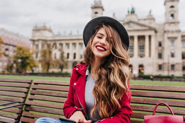 Frohes weibliches modell mit blondem welligem haar, das am wochenendtag auf holzbank sitzt