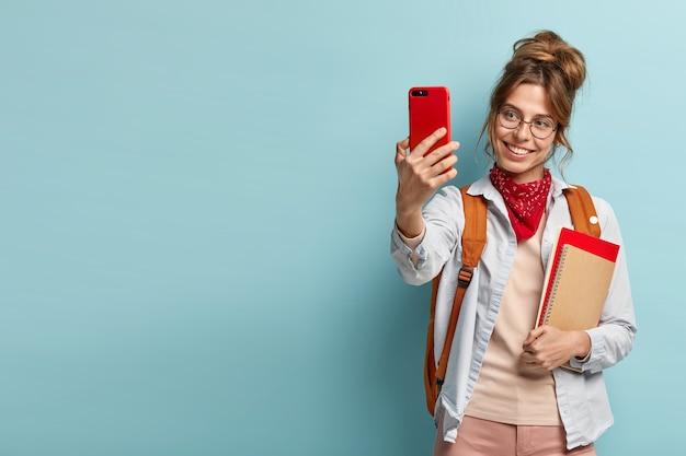 Frohes weibliches modell mit positivem lächeln, macht selfie-porträt auf ihrem handy