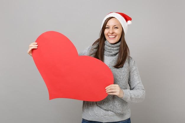Frohes weihnachtsmädchen im grauen pullover, schal weihnachtsmütze halten leeres leeres rotes herz einzeln auf grauem wandhintergrund im studio. frohes neues jahr 2019 feier urlaub party konzept. kopieren sie platz.