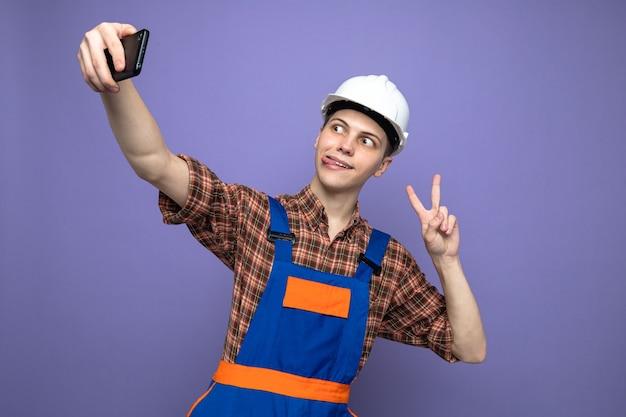 Frohes zeigen von zunge und friedensgeste junger männlicher baumeister, der uniform trägt, macht ein selfie