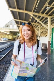 Fröhliche Frau mit Karte auf der Plattform
