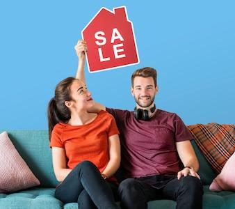 Fröhliche Paare, die eine Hausverkaufsikone halten
