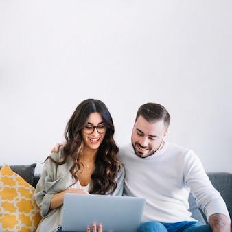 Fröhliche Paare mit Notizbuch auf Sofa