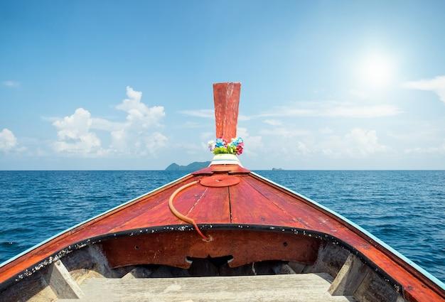 Front-longtail-boot auf blauem meer und himmel