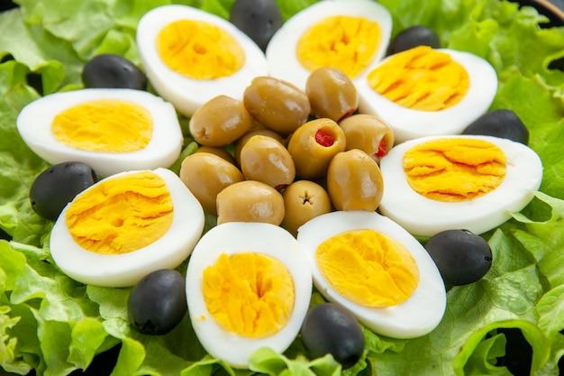 Front nahansicht leckerer eiersalat besteht aus grünem salat und oliven auf hellem hintergrund